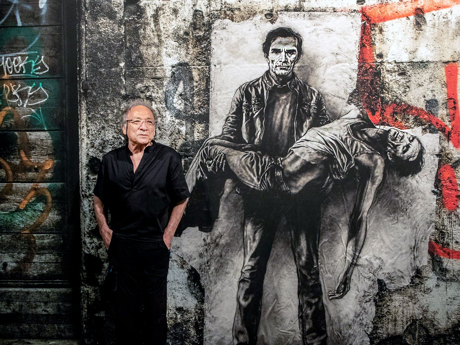 """Ernest Pignon-Ernest next to its iconic portrait of Pasolini during the exhibition """"Ecce Homo"""" in Avignon (2019-2020) which celebrated more than 50 years of artistic expression (©MAXPPP)."""