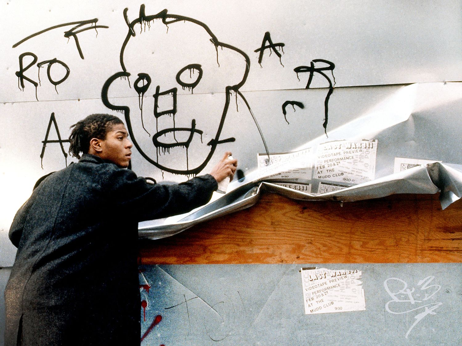 Jean-Michel Basquiat caught in the act of spray painting in the streets of New York for the film Downtown 81 produced between 1980-81 but only broadcasted in 2001 (image taken from the film).